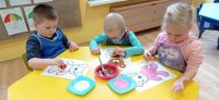 Dzieci malują szablon misia farbami plakatowymi zapomocą gąbki