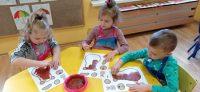 Dzieci wypełniają kontur brzuszka misia farbami plakatowymi zapomocą gąbki