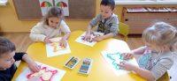 Dzieci rozcierają palcem pokolorowany pastelami kontur misia