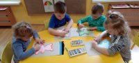Dzieci obrysowują szablon misia pastelami