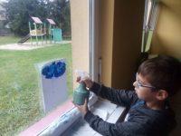 Chłopiec wykonujący deszczowa chmurkę przy pomocy spryskiwacza