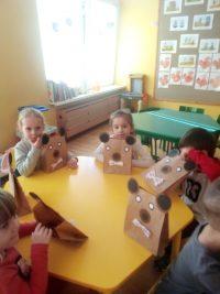 Dzieci siedzące przy stoliku zmisiami wykonanymi zpapierowej torebki iorigamii zkół