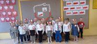 Dzieci wpozycji nabaczność podczas śpiewania hymnu Polski.