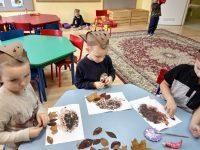 Dzieci wyklejają legowisko jeża zasuszonymi liśćmi