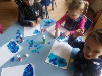 Dzieci wykonujące deszczową chmurkę kawałkami niebieskiej bibuły