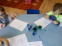 Dzieci wykonujące pracę plastyczna farbą iszczoteczka dozębów