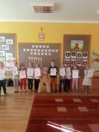 Dzieci stojące zdyplomami zokazji Dnia Pluszowego Misia