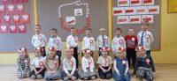Pamiątkowe zdjęcie natle dekoracji przedstawiającej zarys mapy Polski ułożony zbiało-czerwonych kwiatów, flagi igodła Polski wykonane przezdzieci.