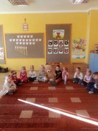 Dzieci siedzące nadywanie zdużym pluszowym misiem