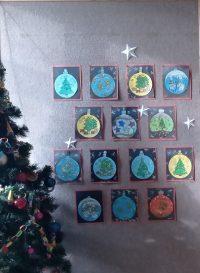 Bombka wykolorowana pastelami, przystrojona brokatem inaklejona naczarną kartkę ozdobioną narysowanymi śnieżynkami.