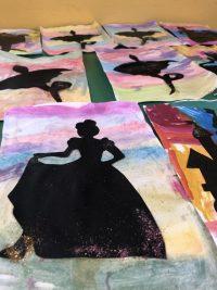 Bajkowe sylwety przyklejone nakartce papieru pomalowanej farbami akwarelowymi.