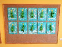 Choinka – choinka wykonana techniką składania papieru, przyklejona nakartkę koloru niebieskiego, ozdobiona bombkami namalowanymi farbami plakatowymi iżółtą gwiazdą wyciętą nożyczkami iprzyklejoną najej czubku, tło ozdobione białą farbą przy pomocy folii bąbelkowej