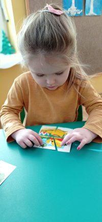 Kubuś Puchatek ijego przyjaciele - dziecko układa obrazek zczęści