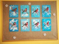Gil – kontur ptaka pomalowany farbami plakatowymi, wycięty nożyczkami iprzyklejony naniebieską kartkę papieru, śnieg pomalowany białą farbą przy pomocy folii aluminiowej