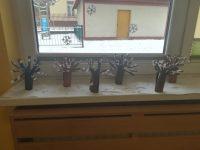 Zimowe drzewko naparapecie – praca wykonana jest zrolki papieru toaletowego, naklejonej naniej czarnej lub brązowej kartki zbloku technicznego wyciętej dopołowy paskami, naklejonymi nagałęziach kawałkami białego papieru śniadaniowego