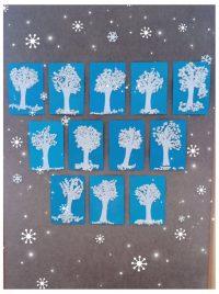 Zimowe drzewo - pień drzewa wycięty zbiałego papieru inaklejony naniebieską kartkę, śnieg wykonany zkawałków białej bibuły
