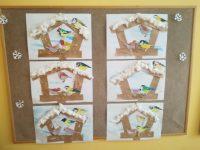 Ptaki wkarmniku - kartka zdużego bloku technicznego pomalowana białą pastą dozębów zfragmentami niebieskiej farby plakatowej, następnie przyklejony karmnik wykonany zwyciętych pasków papieru pakowego, postacie ptaków pokolorowane pastelami olejnymi, wycięte iprzyklejone wkarmniku, ziarenka naklejone wśrodku karmnika, dach karmnika pokryty watą.