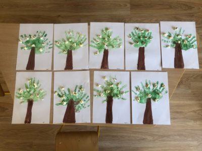Wiosenne drzewa- praca wykonana poprzez odcisk dłoni wzielonej farbie, kwiaty zpopcornu.